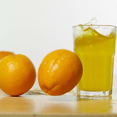 Appelsiineja ja juomalasi pöydällä.