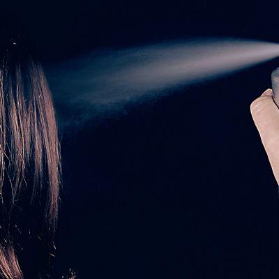 Nainen suihkuttaa hiuslakkaa hiuksiinsa.