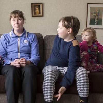 Kortteen perhe istuu sohvalla