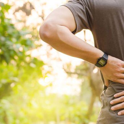 Mies pitää käsillään kipeää selkäänsä kesken juoksulenkin.