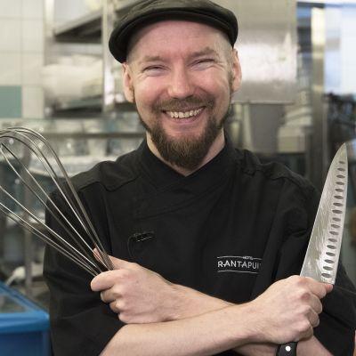 Kokki Mika Ahlfors poseeraa keittiössä käsikirjoitettuaan, ohjattuaan ja tuotettuaan Punasii päin - nimisen elokuvan.