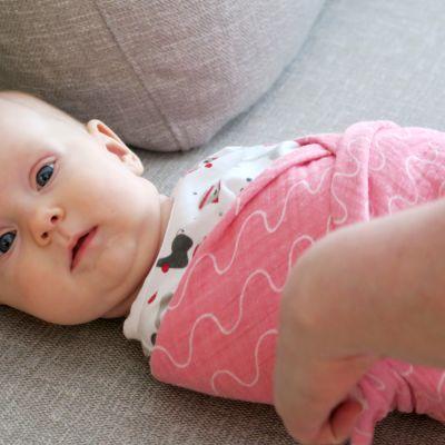 Vauva kapaloituna vaaleanpunaiseen kapaloon.