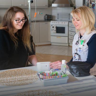 Sairaanhoitaja Heidi Rosbäck mittaa Meri Myllykankaalta verenpainetta.
