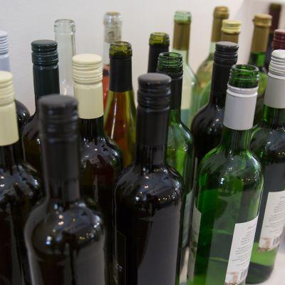 Viinipulloja pöydällä.