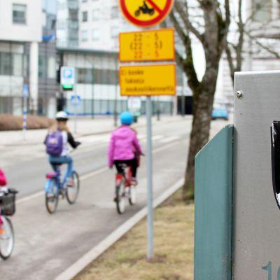 Kouvolan vaakuna kyltissä, taka-alalla pyöräileviä lapsia.
