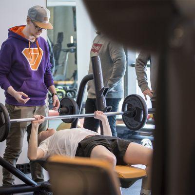 Mies nostaa painoja, valmentaja ohjaa