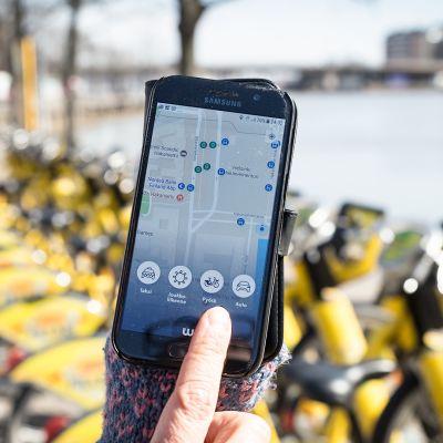 Whim-mobiilisovellus älypuhelimen näytöllä, taustalla kaupunkipyöriä.