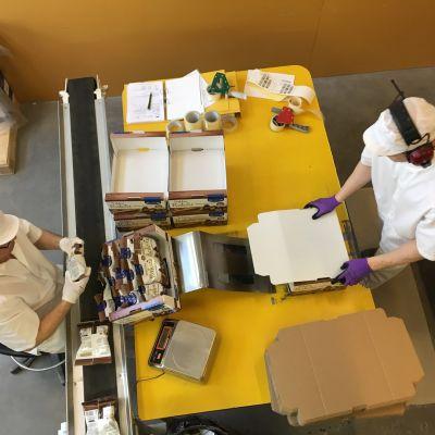 Kaksi ihmistä laittaa tehtaalla karkkipusseja laatikoihin.
