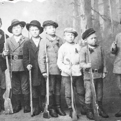 """Kymin """"pikkupunakaartilaisia"""" vuonna 1918. Seitsemän pikkupoikaa leikkiaseineen. Yhdellä pojista oikea ase."""