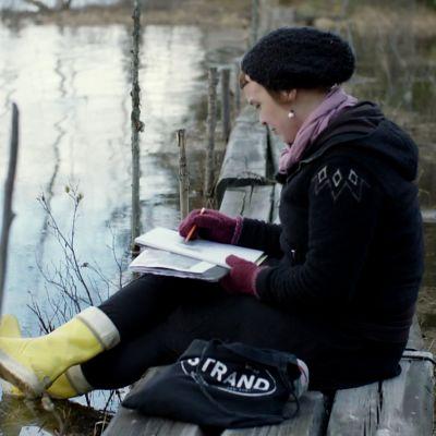 Hanneriina Moisseinen piirtää järven rannalla