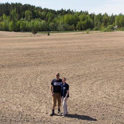 Maanviljelijäpariskunta pellolla.