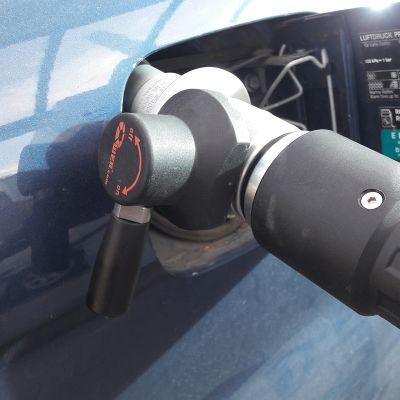 Kaasutankkausaseman tankkauspistooli kiinnitettynä auton tankkiin.