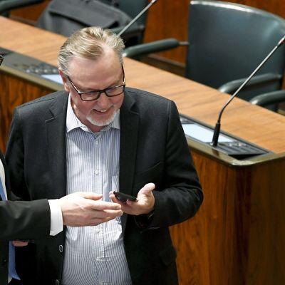 Pääministeri Juha Sipilä ja kansanedustaja  Antero Laukkanen (kd.) tutkivat kännykkää eduskunnan täysistunnossa.