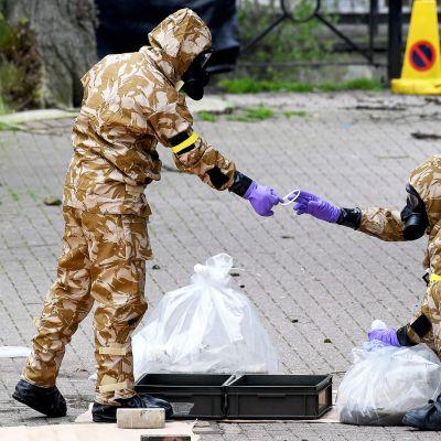 Suojavarusteisiin pukeutuneita sotilaita tekemässä rikospaikkatutkintaa.