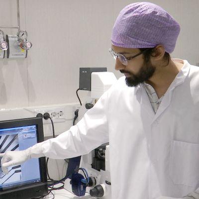 Tutkija osoittaa tietokoneen ruutua.