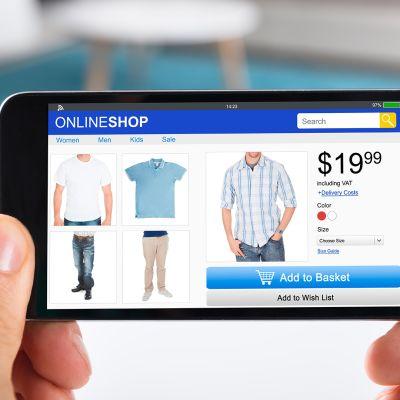 Mies selaa verkkokaupan tuotteita älypuhelimella.