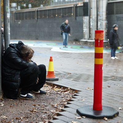 Mies nukkuu seinänvierustalla Helsingissä.