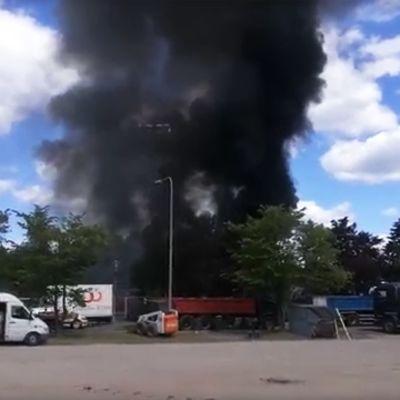 Musta savupatsas kohoaa taivaalle.