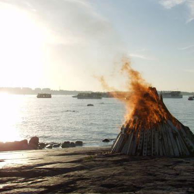 En midsommarbrasa som brinner på en strandklippa.