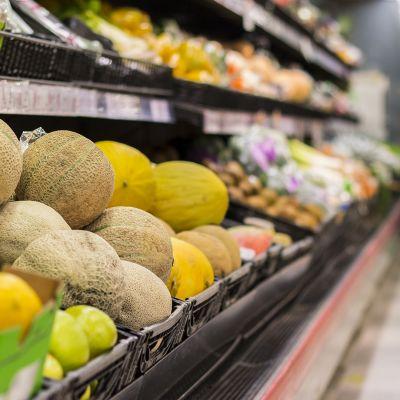 Kuva kaupan hedelmäosastolta. Etualalla on cantaloupe-meloneja
