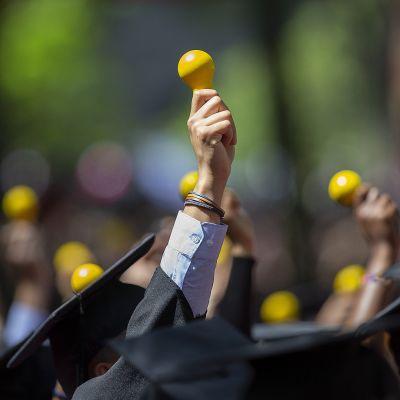 Harvardin valmistuvia opiskelijoita - lähikuva kädestä, joka pitelee hehkulampun muotoista symbolia.