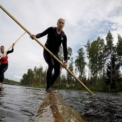 Iida Mäntylä ja Milla Sulkakoski tasapainoilevat tukkien päällä joessa.