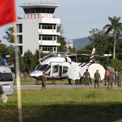 Sotilaat ja poliisit siirtävät luolasta pelastettua poikaa pelastushelikopterilla.