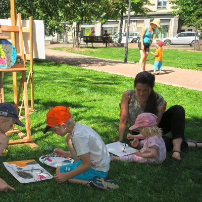 Ihmisiä maalaamassa ulkona.