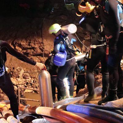 Thaimaalaiset sukeltajat kantavat sukellusvarusteita luolaan.