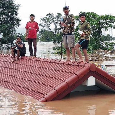 Miehet seisovat tulvaveden valtaaman talon katolla Laosissa.