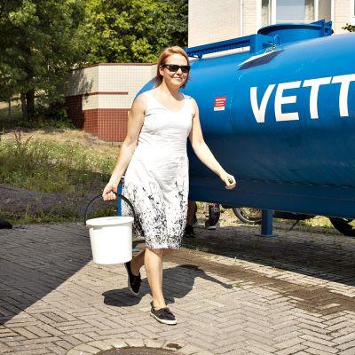 Natalja Suotula-Gröndahl hakemassa vettä Naantalin terveysaseman pihalle vedenjakeluhäiriöiden takia tuodusta vedenjakelupisteestä 31. heinäkuuta.