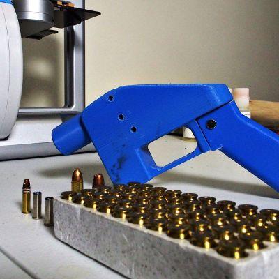 Kuvassa pistoolin edessä on 3D-tulostin, jolla pistoolin osat on valmistettu.