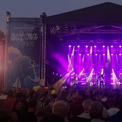 Elastinen Kemin Satama Open Air -festivaaleilla. Kuvassa näkymä värivaloin valaistulle lavalle, jossa esiintyjä orkesterinsa kanssa.