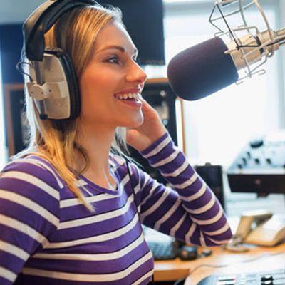 Naisjuontaja radiostudiossa.