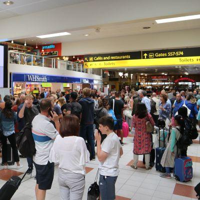 Matkustajia Gatwickin lentoasemalla 20. elokuuta, jossa lentotiedot ilmoitettiin tussitauluilla.