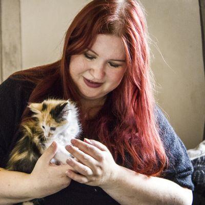 Nainen pitää sylissään kissanpentua.