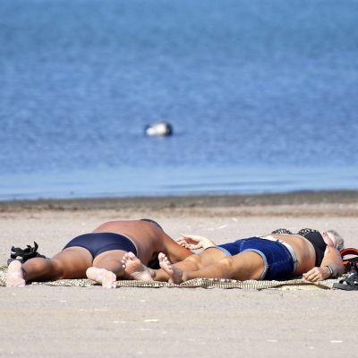 Auringonottajia rannalla.