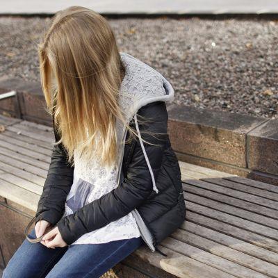 Nuori tyttö istuu yksin penkillä.