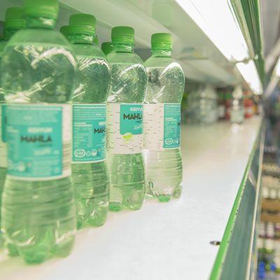 Hyvinvointivesipulloja kaupan hyllyllä.