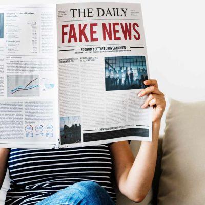 Nainen lukee lehteä, jossa on valeuutisia.