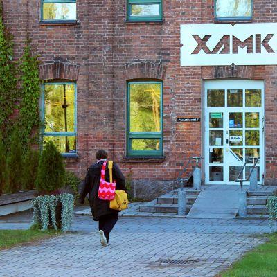 Nainen kävelee kohti Xamkin Kouvolan kampuksen pääovea