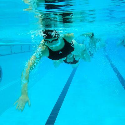 Uimareita kuvattu veden alla Lappeenrannan uimahallissa.