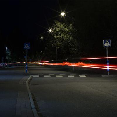 Pimeällä kadulla pitkällä valotusajalla otetussa valokuvassa auton valojen jättämät viirut.