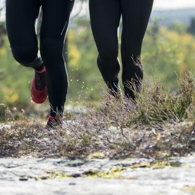 Vesi roiskuu juoksijoiden kengistä.