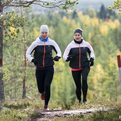 Kaksi naista juoksee metsäpolulla.