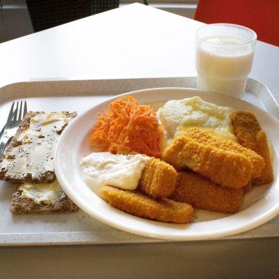 Lautasella on kalapuikot ja muusi, maitoa ja näkkileipää.