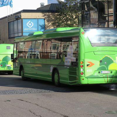 Kaksi bussia ajaa peräkkäin Jyväskylän keskustassa.