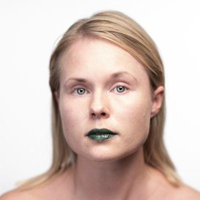 Suoraan kameraan katsovan naisen huulet on maalattu vihreällä.