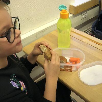 Koululainen syö eväitä luokassa.