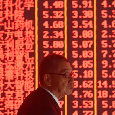 Kiinalainen pörssimeklari pörssikursseja esittävän valotaulun edessä.